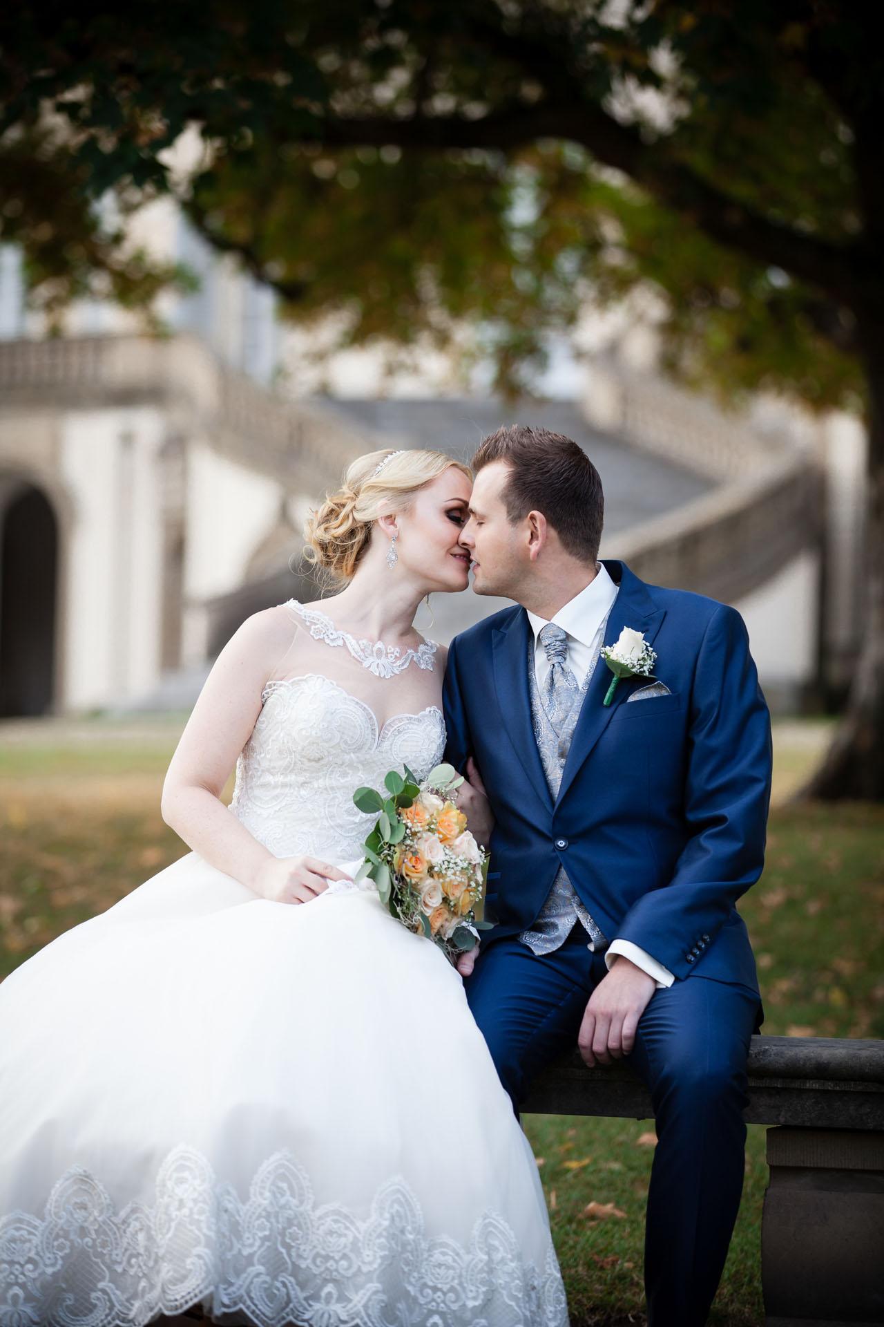 Braut und Bräutigam küssen sich vor dem Schloss Solitude in Stuttgart