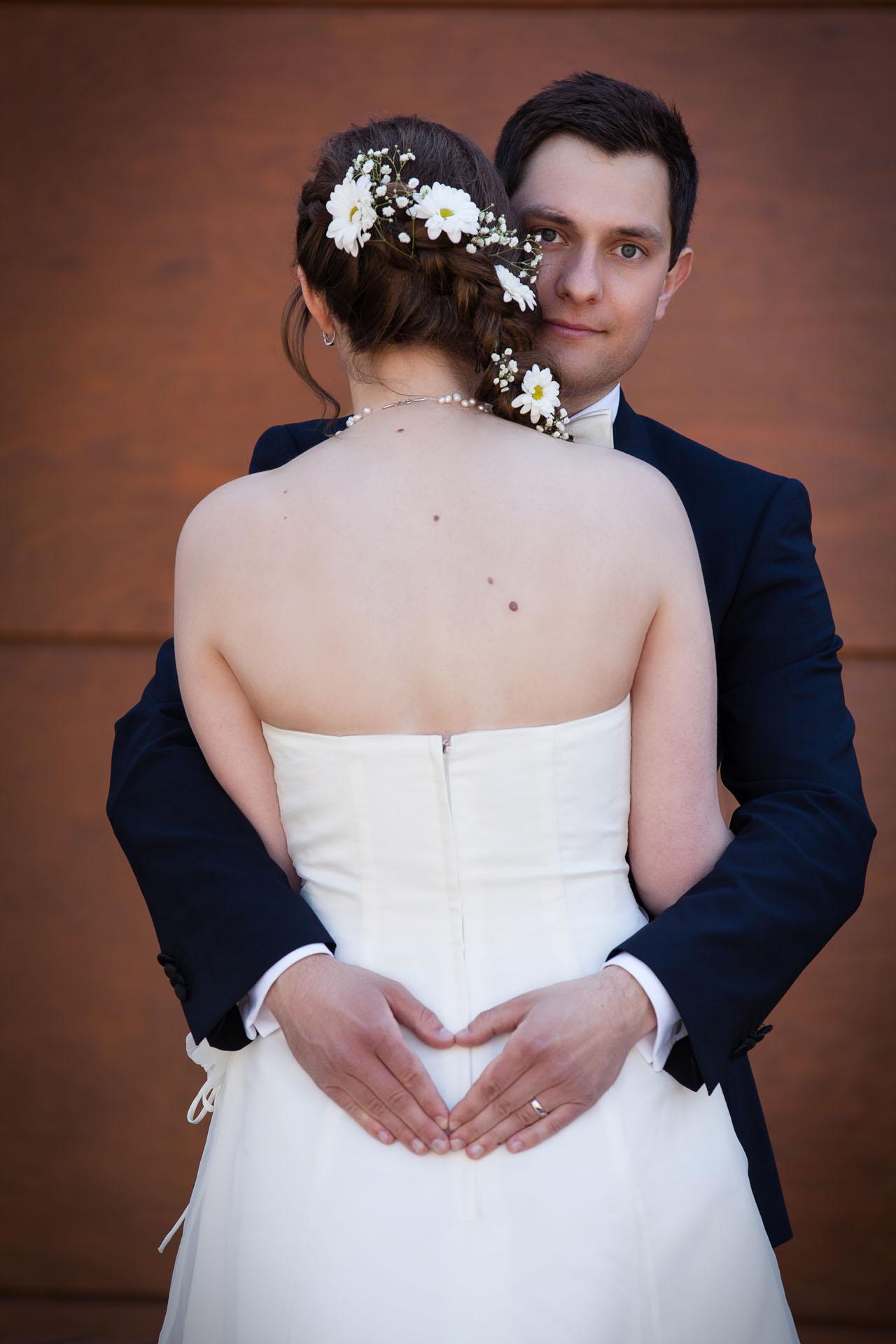 Bräutigam umarmt Braut und schließt mit den Händen eine Herzform