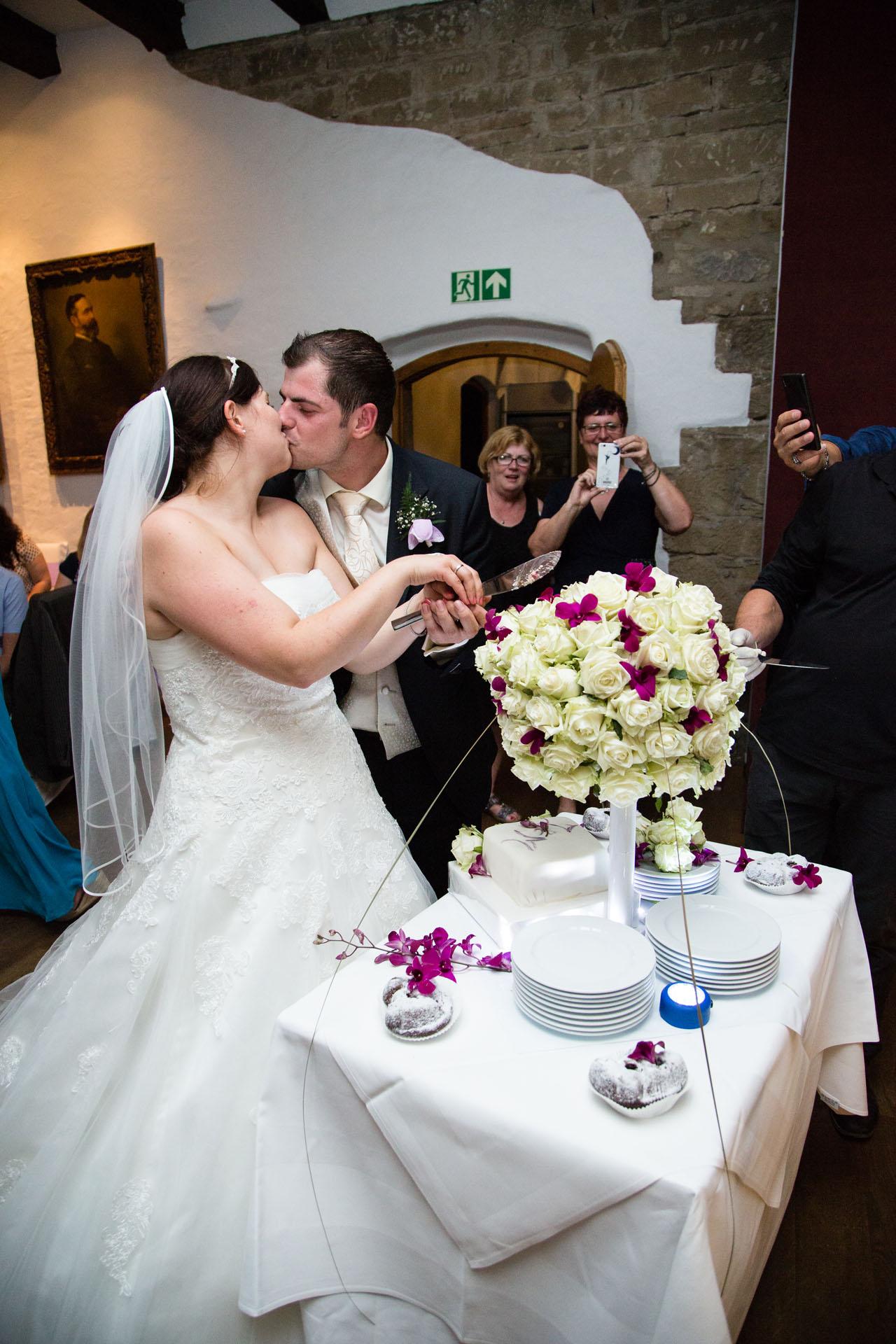 Hochzeitstorte aus Rosen wird angeschnitten